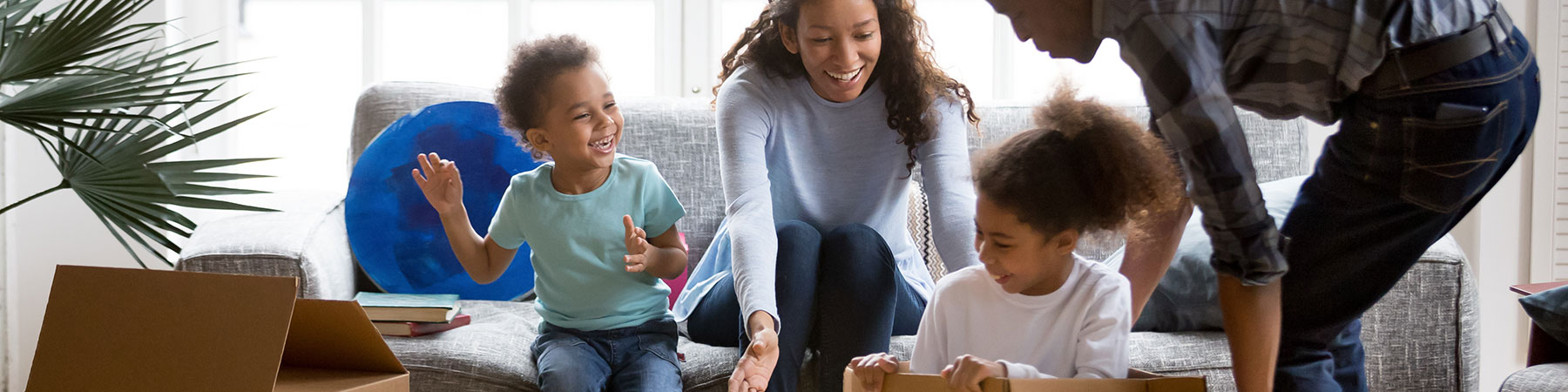 family playing with boxes in living room of new home